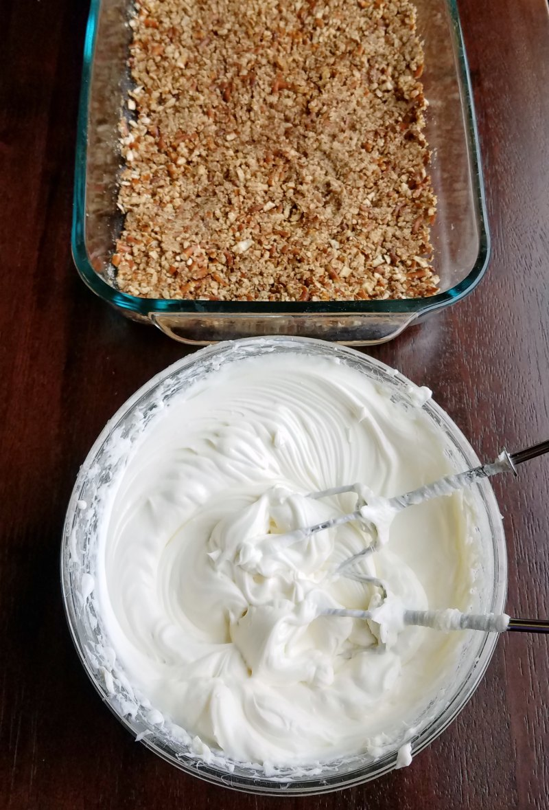 pretzel crust with bowl full of whipped cream cheese