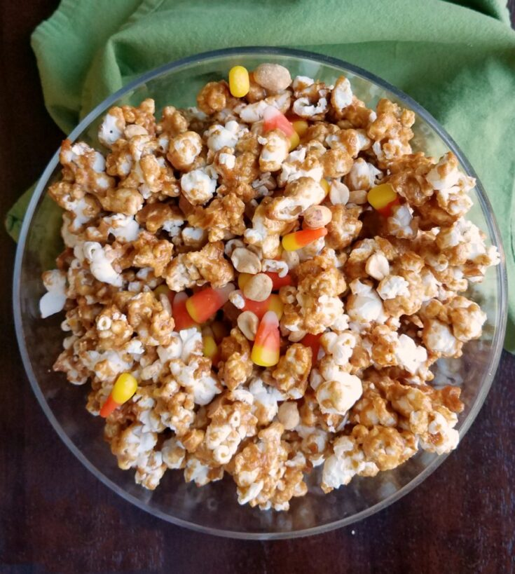 Bowl of peanut butter popcorn with peanuts and candy corn.