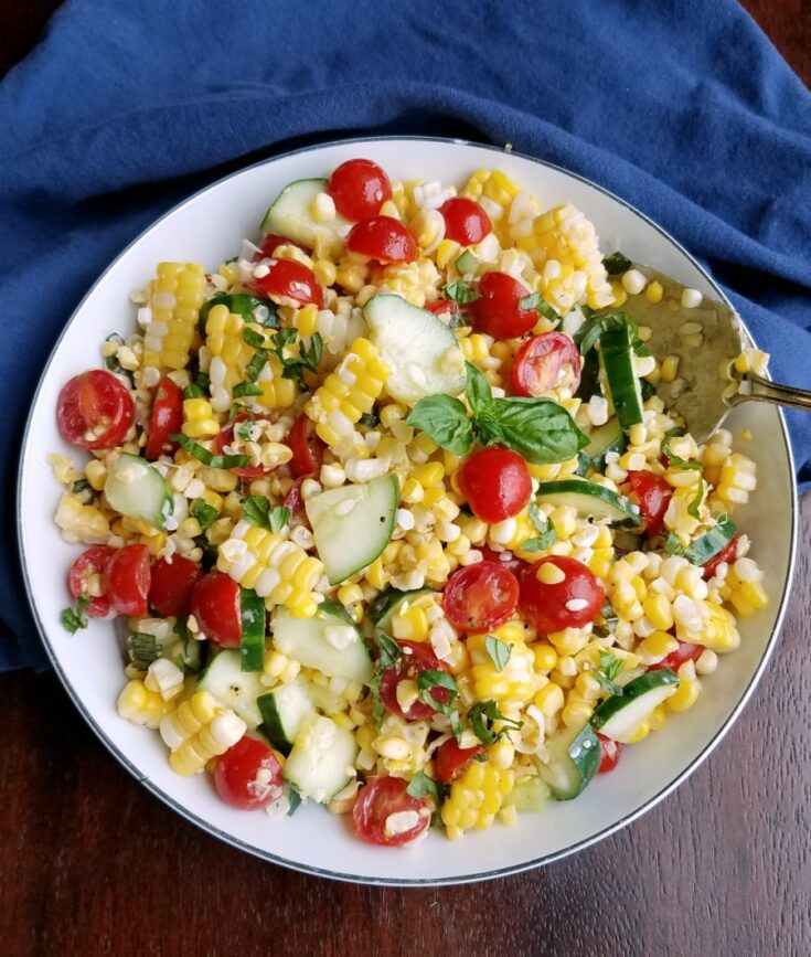 Bowlful of corn salad with cherry tomatoes, basil, cucumbers and fresh corn.