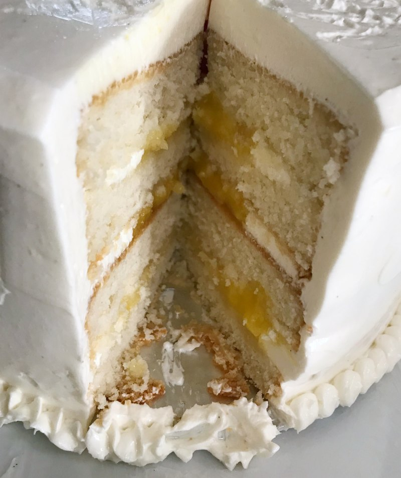 four layers of white cake with white frosting and lemon curd filling in a stacked cake with a piece missing to reveal the middle.