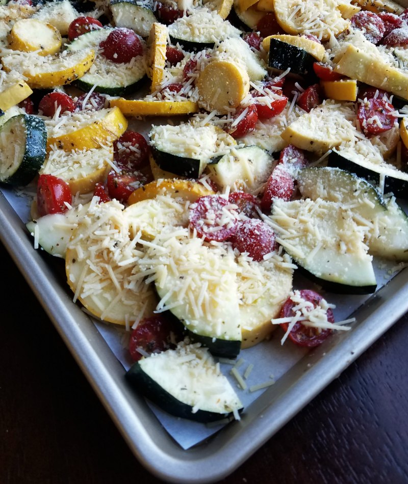 marinated zucchini and tomatoes covered with grated Parmesan ready to roast.