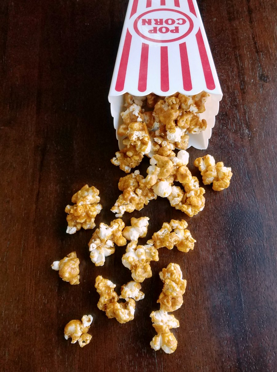 popcorn container spilled over with peanut butter popcorn coming out