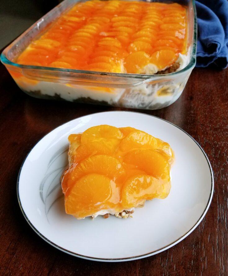 Pretzel salad with cream cheese center and orange jello toppings.