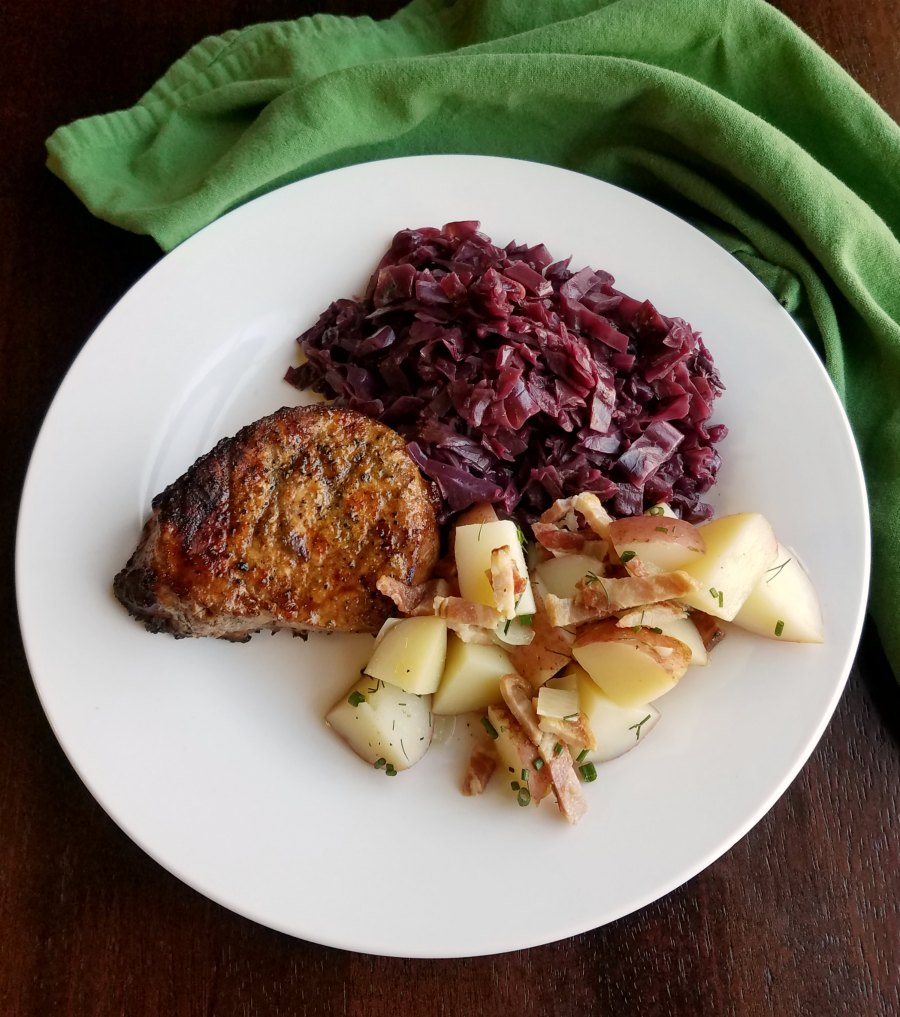 dinner plate with braised cabbage pork loin and german potato salad