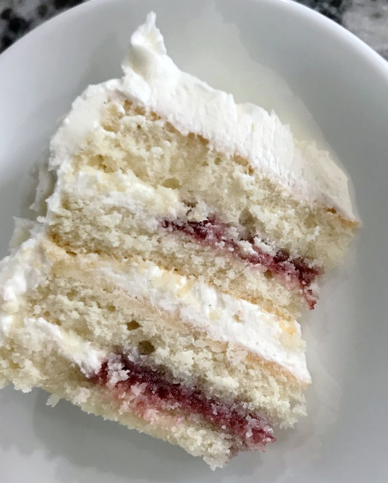 slice of cake with 4 layers of white cake, white frosting and raspberry filling.