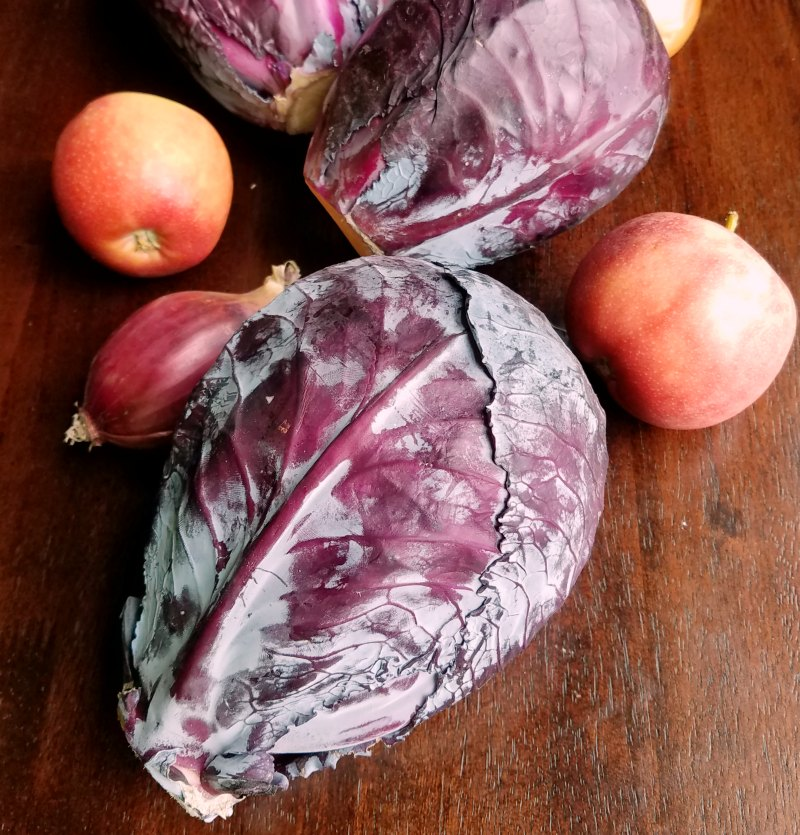 heads of red cabbage, apples and onions