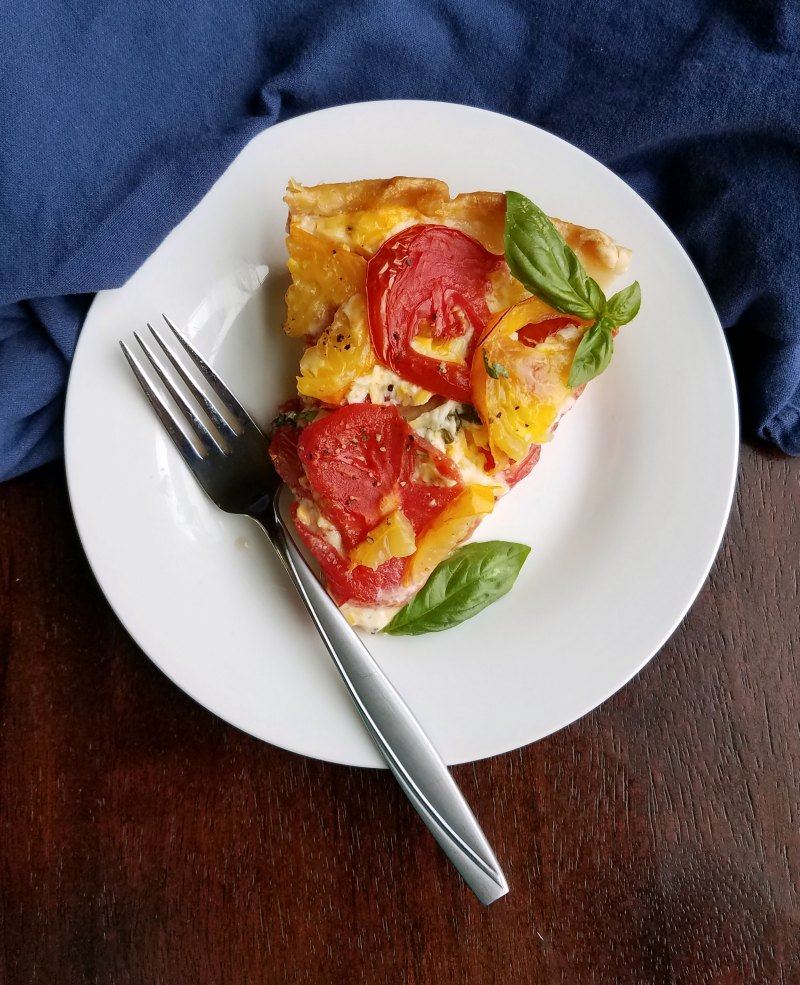 slice of cheesy tomato pie with basil and fork
