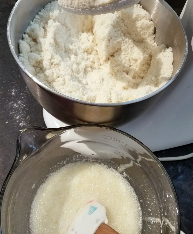 mixer full of dry ingredients with bowl of we ingredients for bakery style white cake.