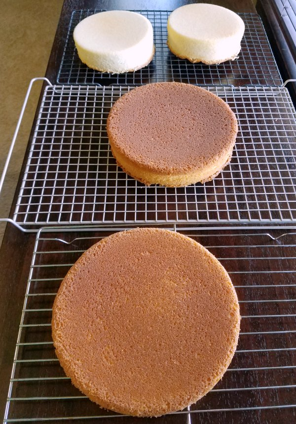 White cake layers cooling on wire racks.