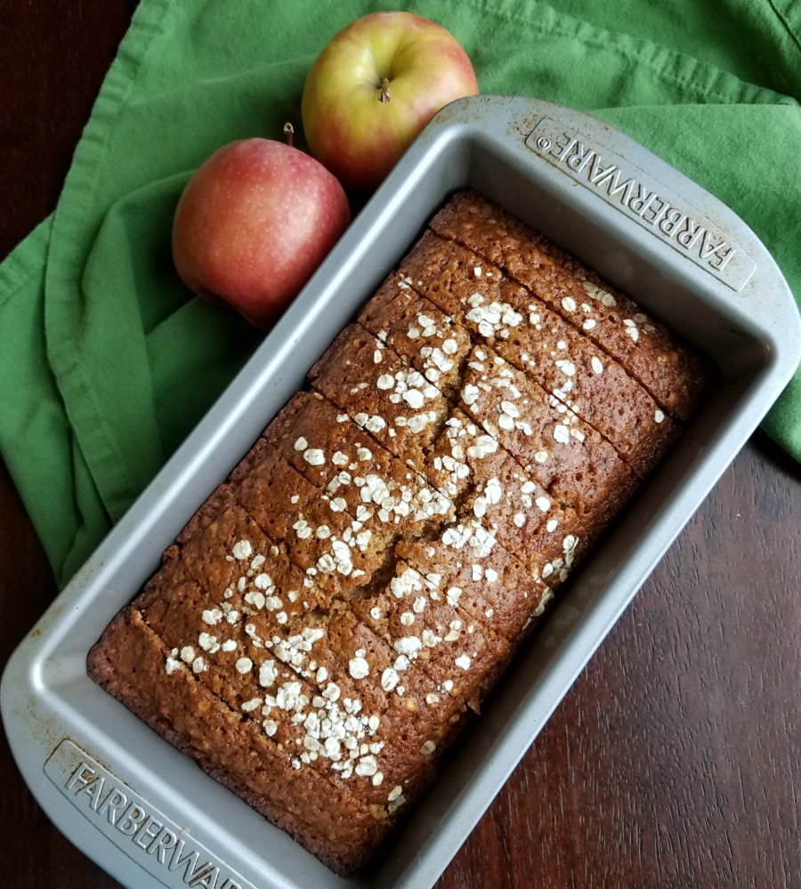 sliced loaf of applesauce oatmeal quick bread back in loaf pan with apples.