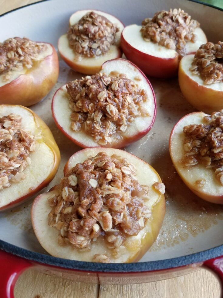 pan filled with baked apple halves topped with oatmeal mixture