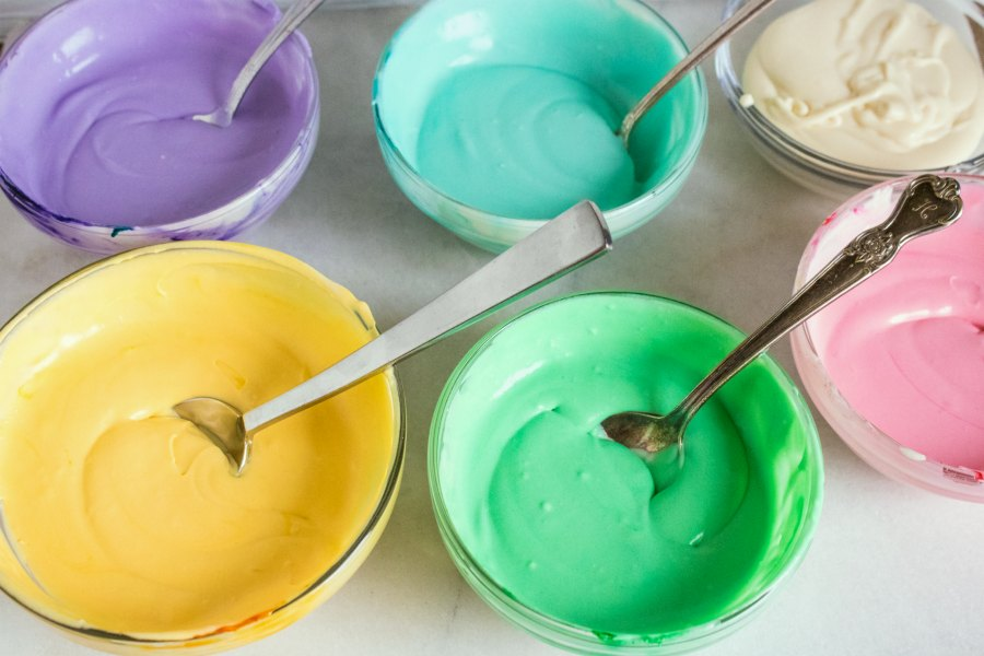 small bowls of various colors of ice cream base.