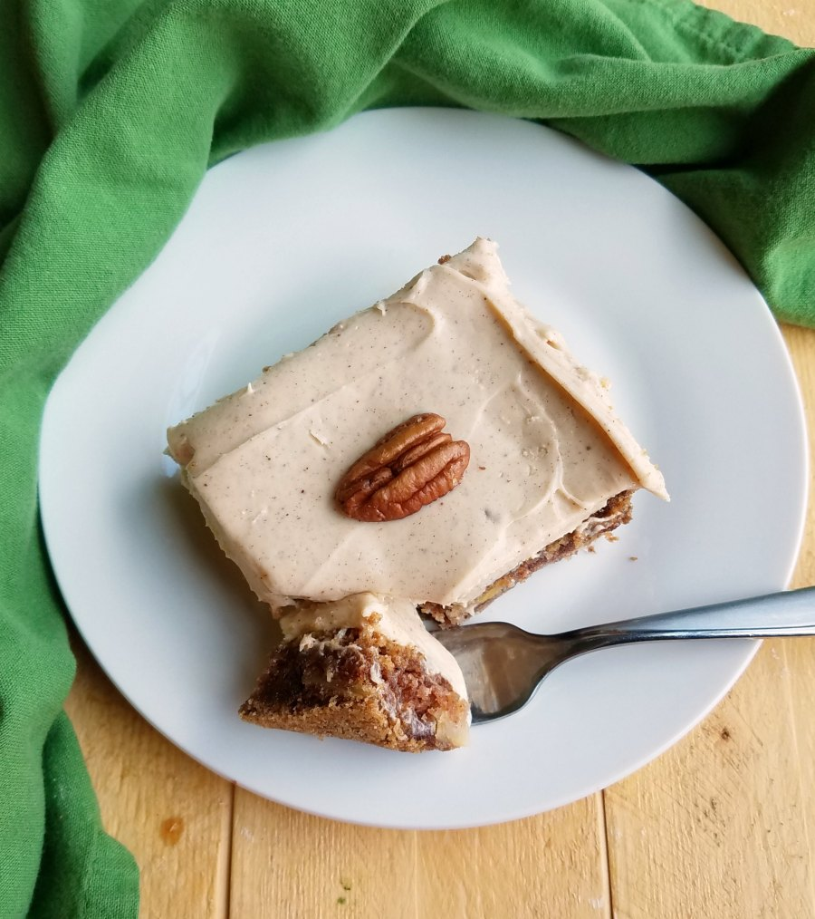 piece of cake covered with cinnamon brown sugar cream cheese frosting and topped with a pecan half