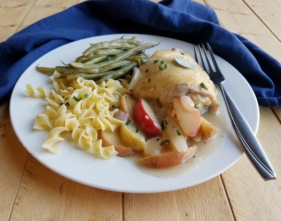 dinner plate with chicken and apples, buttered noodles and green beans, side view.