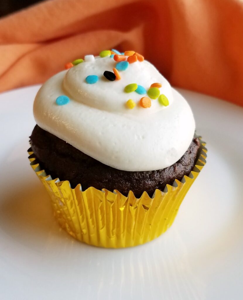 chocolate pumpkin cupcake topped with smooth white whipped sweetened condensed milk frosting.