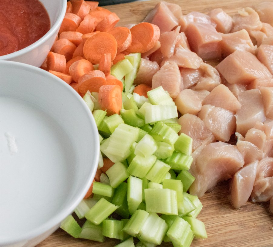 cutting board with diced celery, carrots and chicken.