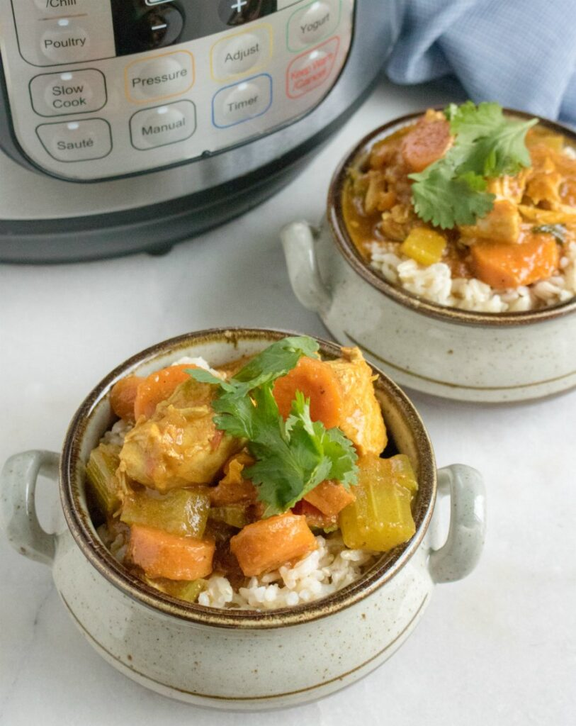 chicken and vegetable curry served over rice in front of instant pot.