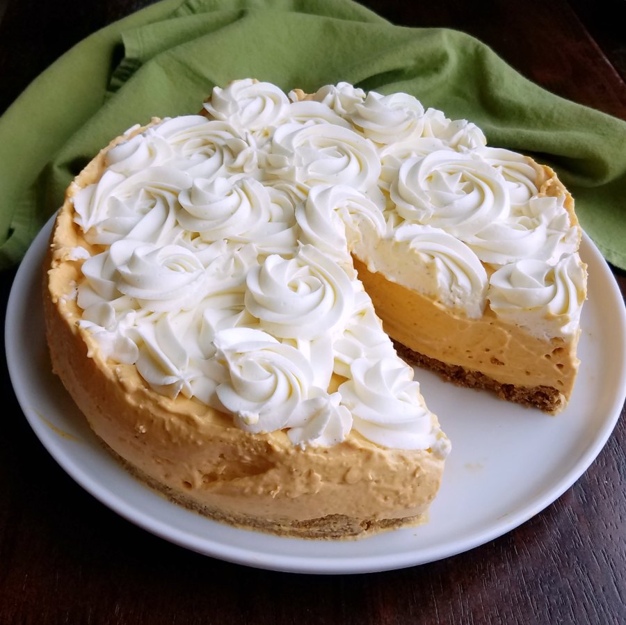 No bake pumpkin cheesecake with rosettes of cream cheese whipped cream on top, with one slice missing.