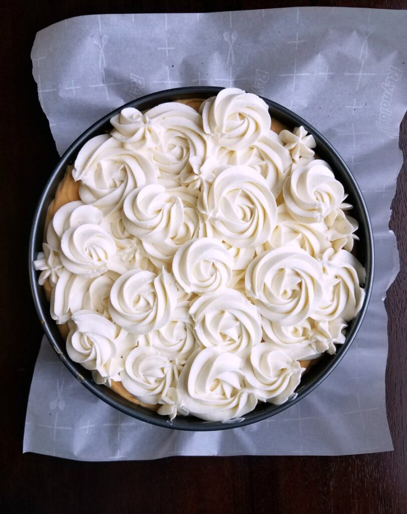 Rosettes of white whipped cream mixture on top of cheesecake.