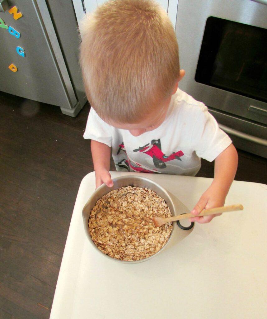 little dude stirring bowl of cinnamon oatmeal to bake.