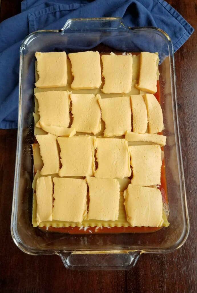 lasagna noodles with slices of Velveeta cheese on them, middle layer of lasagna