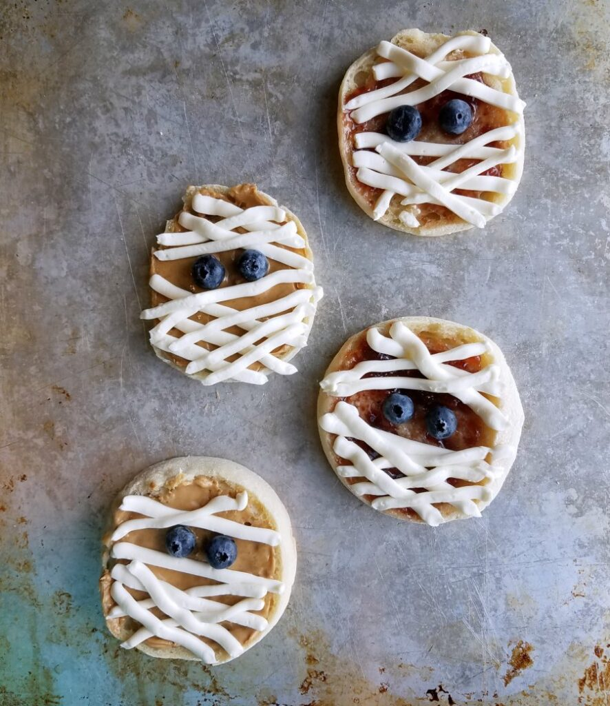 English muffin mummies with peanut butter, jelly and cream cheese and blueberry eyes ready to eat.