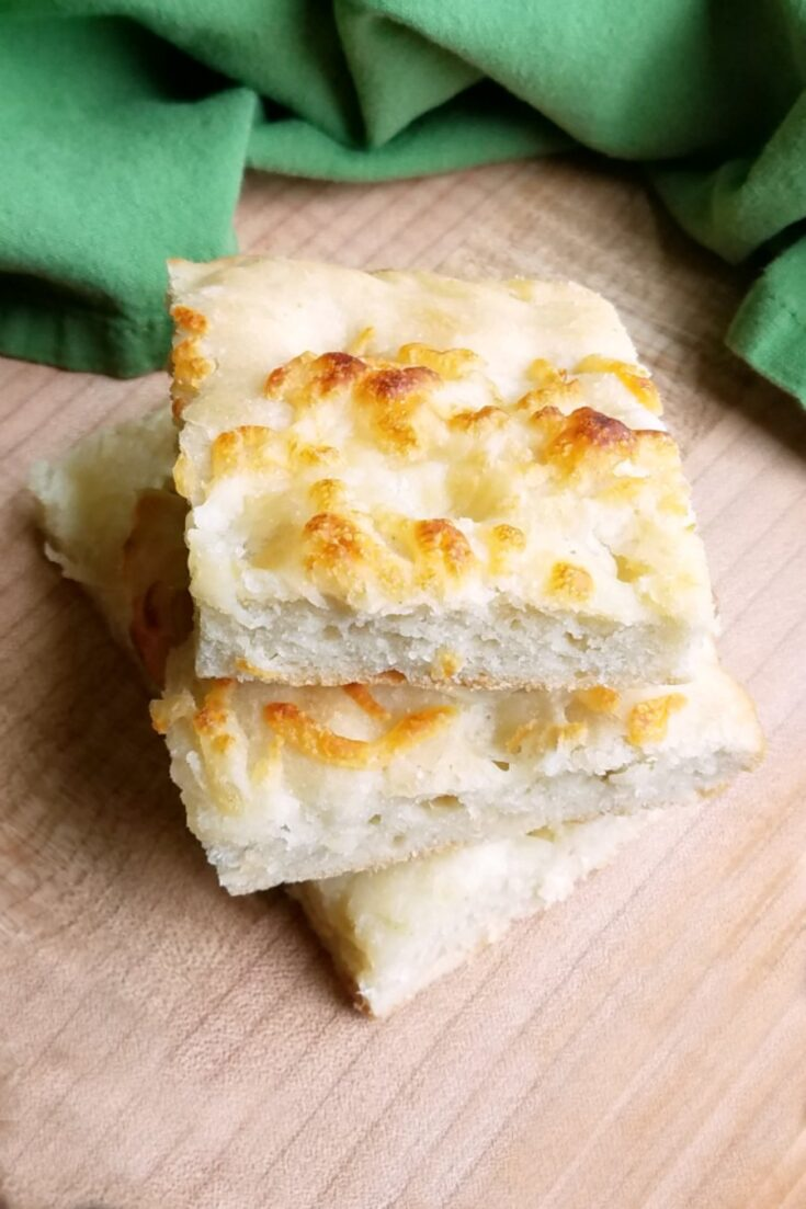 Soft and chewy sourdough foccacia topped with cheese and garlic is the perfect side for any Italian meal. It's like one big giant bread stick only easier to make!