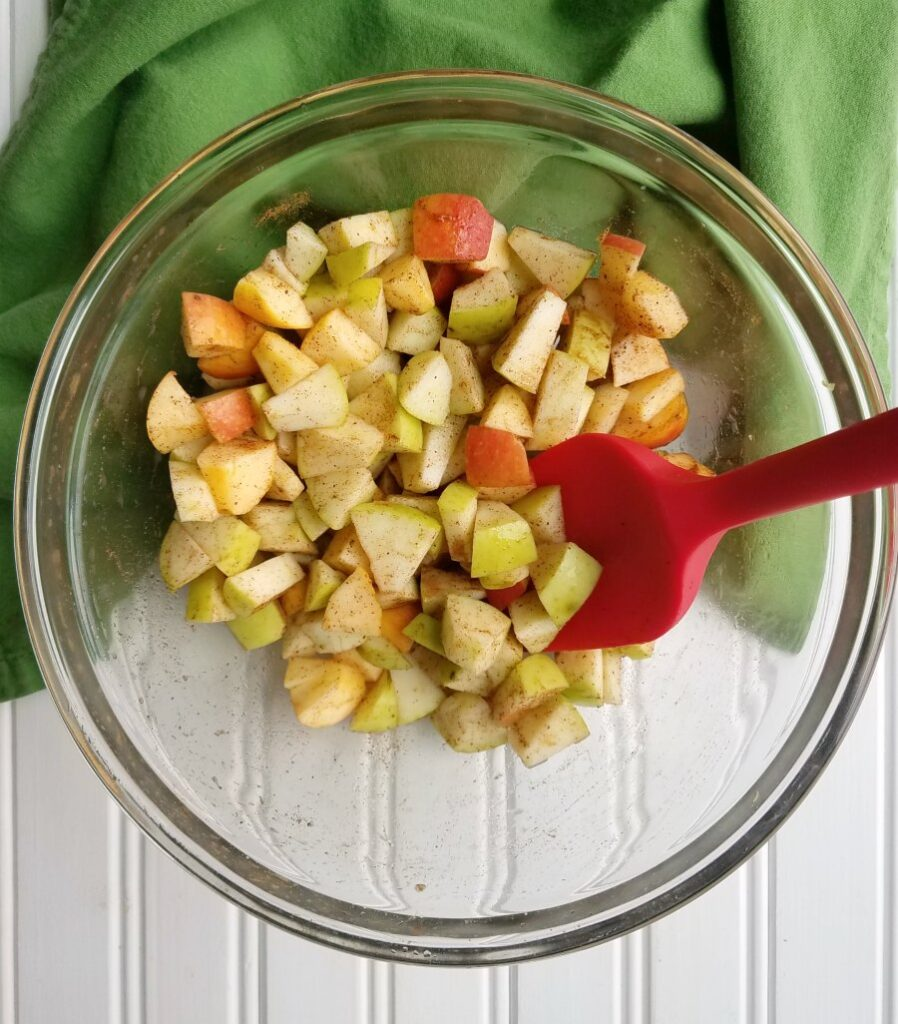 chunks of apple in mixing bowl coated with spices.
