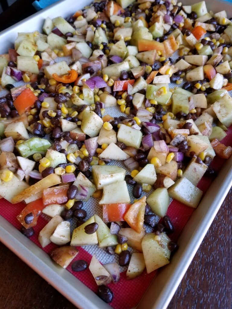 sheet pan filled with diced veggies and black beans.