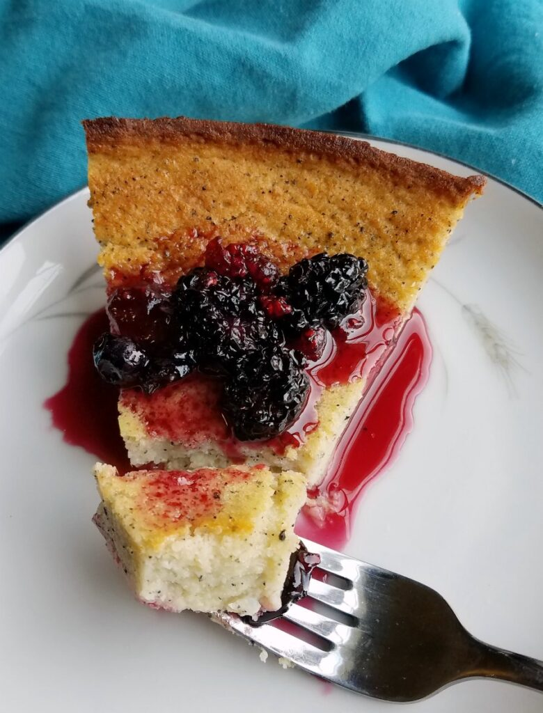 Bite of creamy dragon fruit pie with blackberry sauce on fork ready to eat.