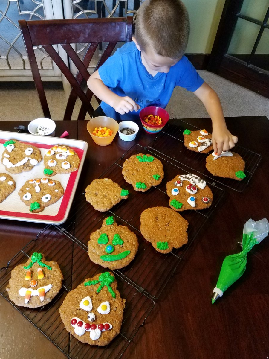 kid decorating pumpkin cookies with frosting and candy