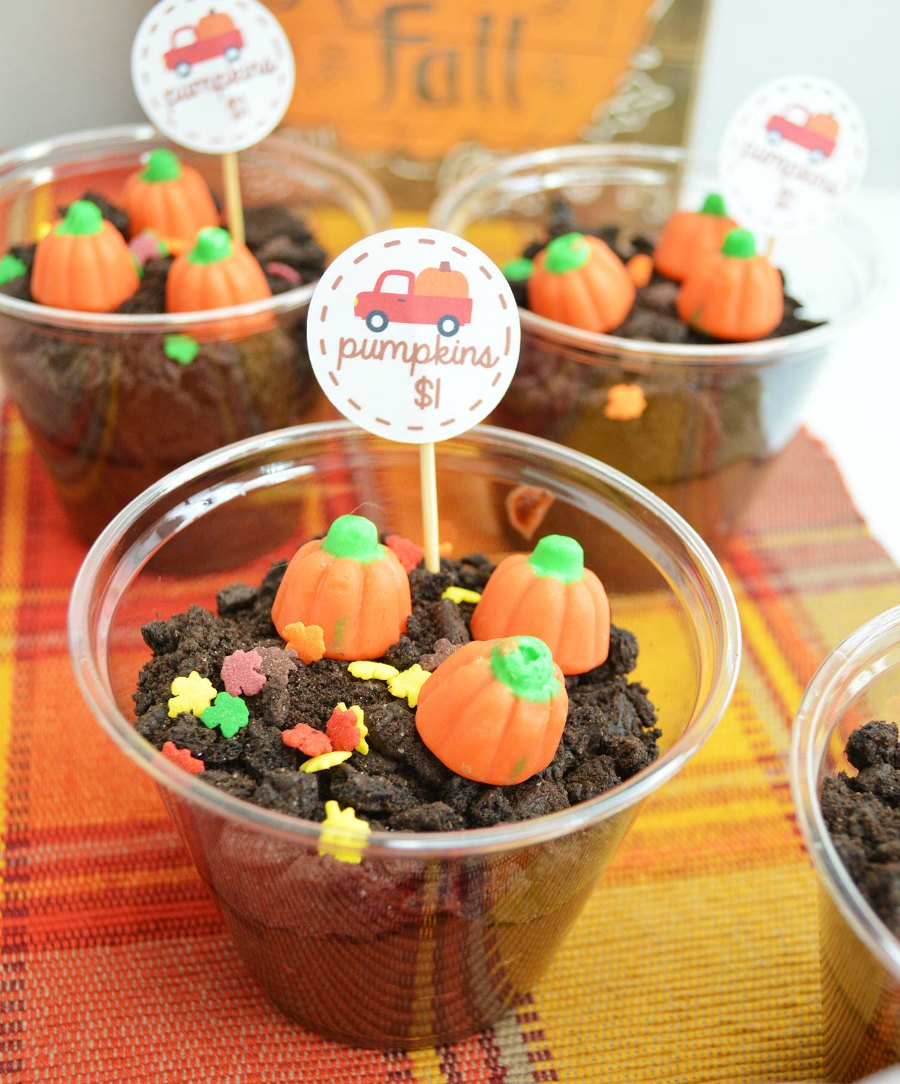 plastic cups with individual servings of chocolate dirt pudding with candy pumpkins on top