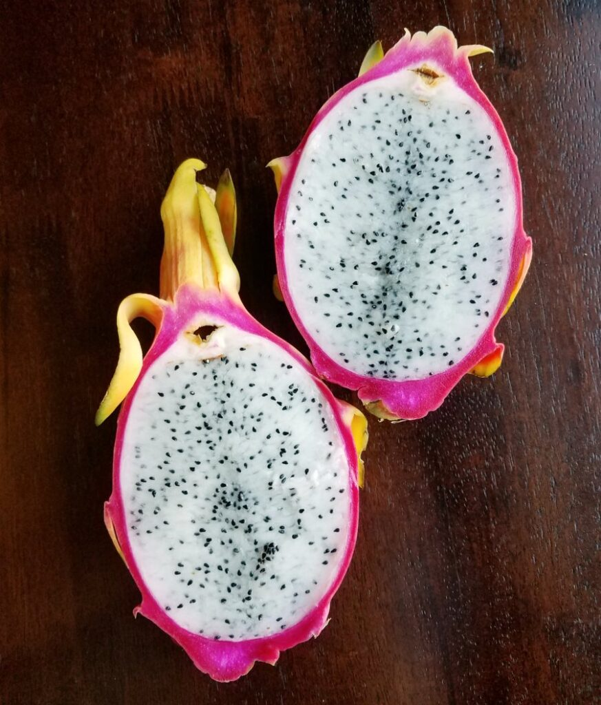 inside of dragon fruit with bright pink exterior, white flesh and black specks for seeds.