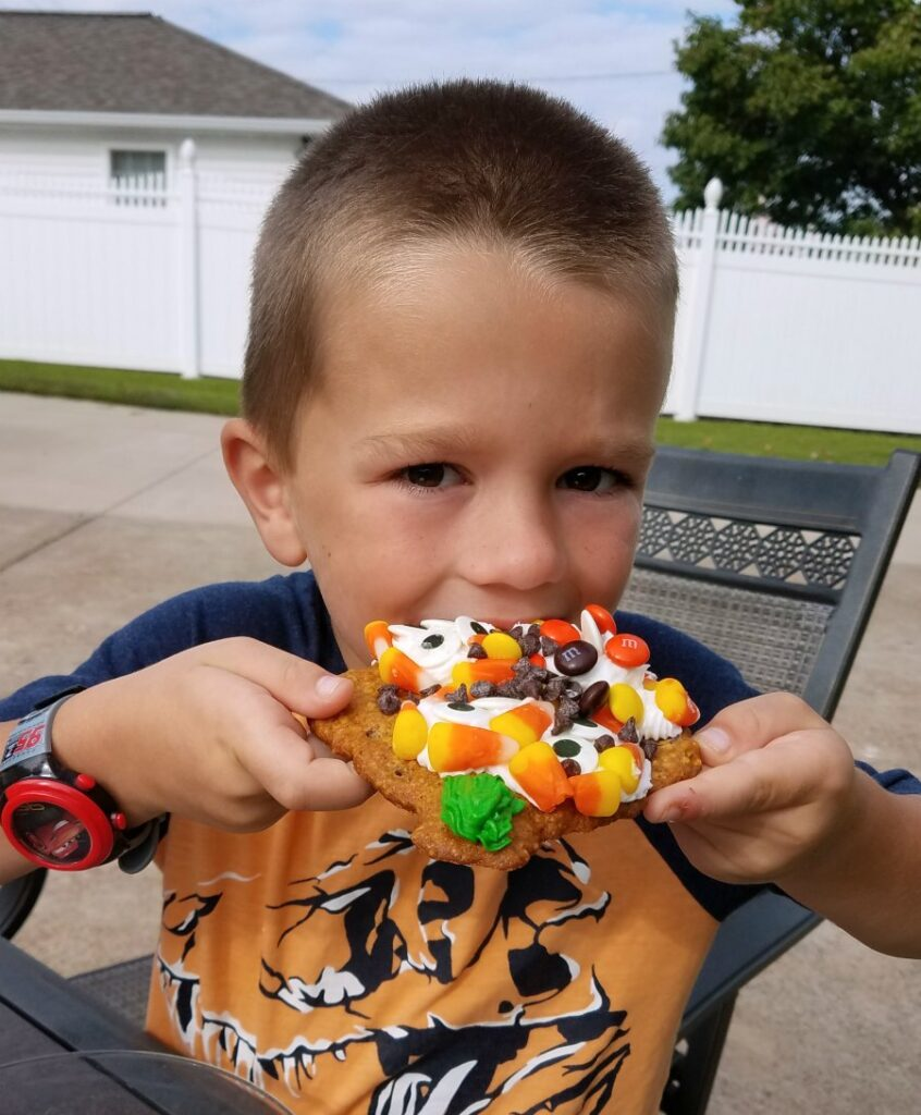 kid eating a cookie loaded with frosting and candy.