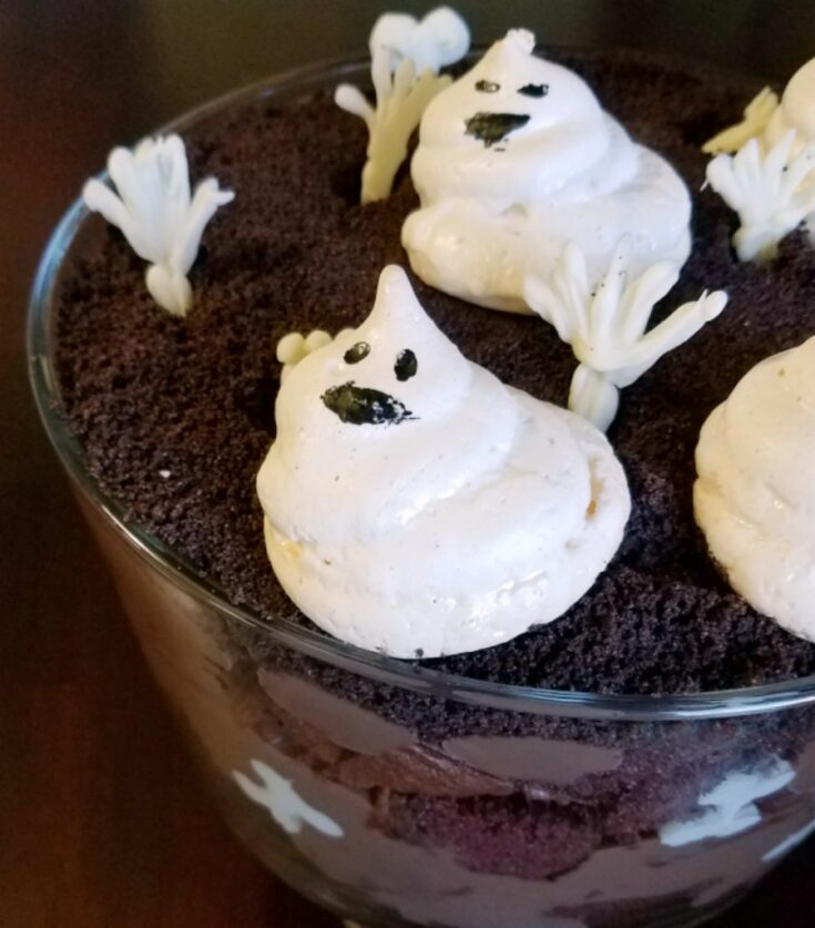 layers of chocolate in glass trifle bowl with white chocolate hands and meringue ghosts on top.