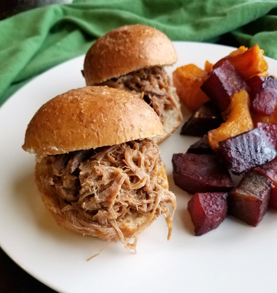 2 pulled pork slider next to a pile of roasted veggies