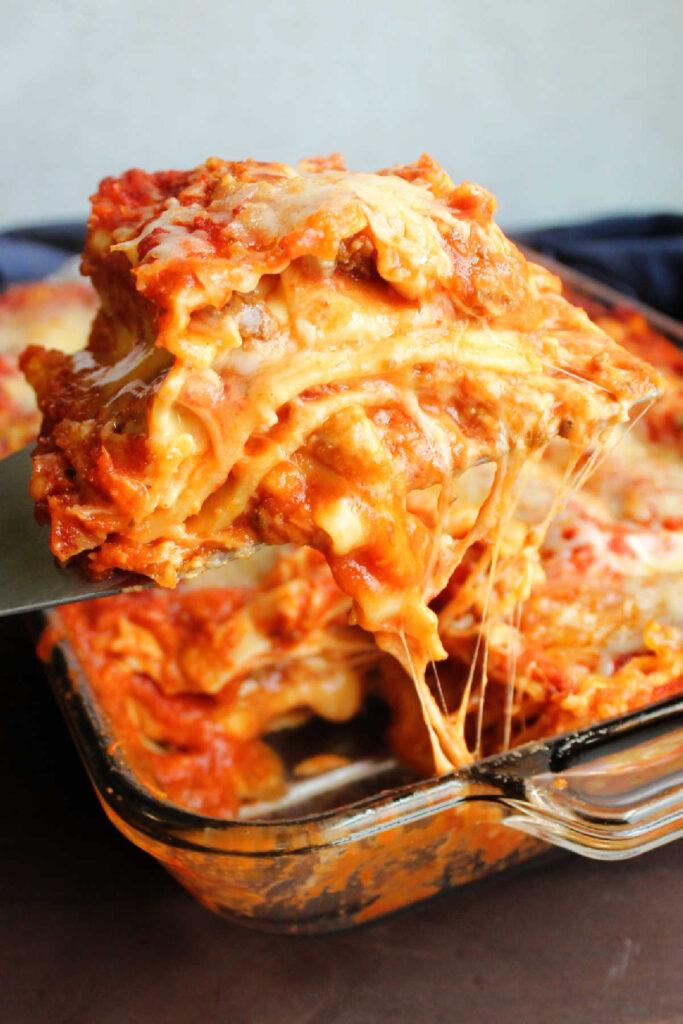 Lifting slice of gooey cheesy Velveeta lasagna out of pan.