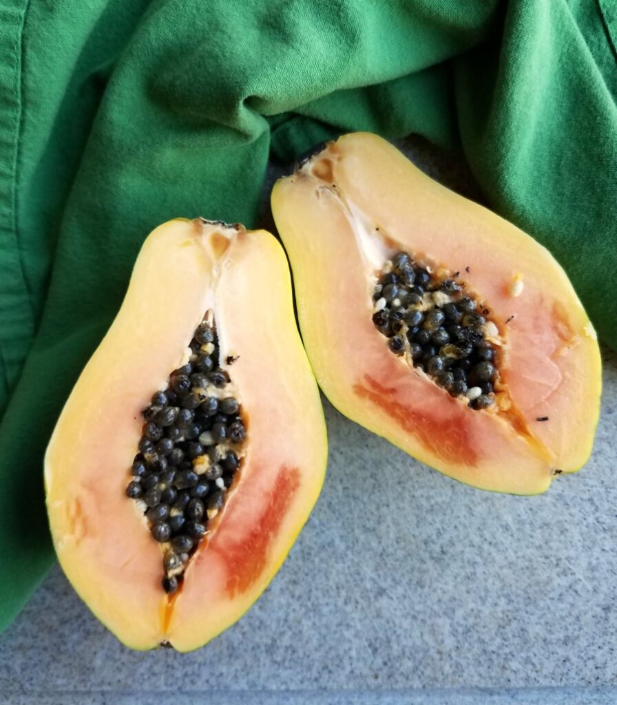 strawberry papaya cut in half with black seeds in center.