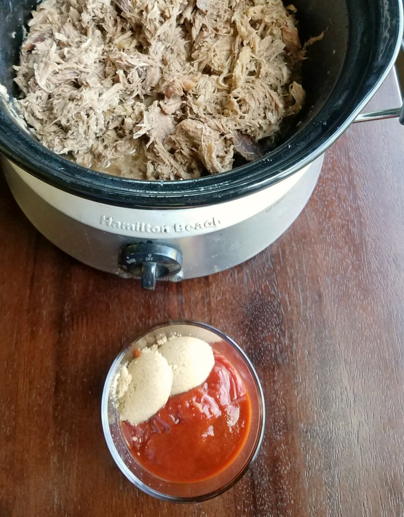 slow cooker filled with pulled pork with bowl of ingredients for sriracha sauce.