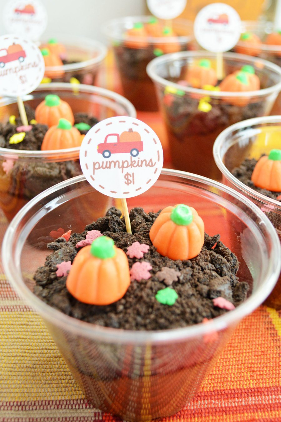 close up of plastic cups filled with dirt pudding and cute pumpkin decorations