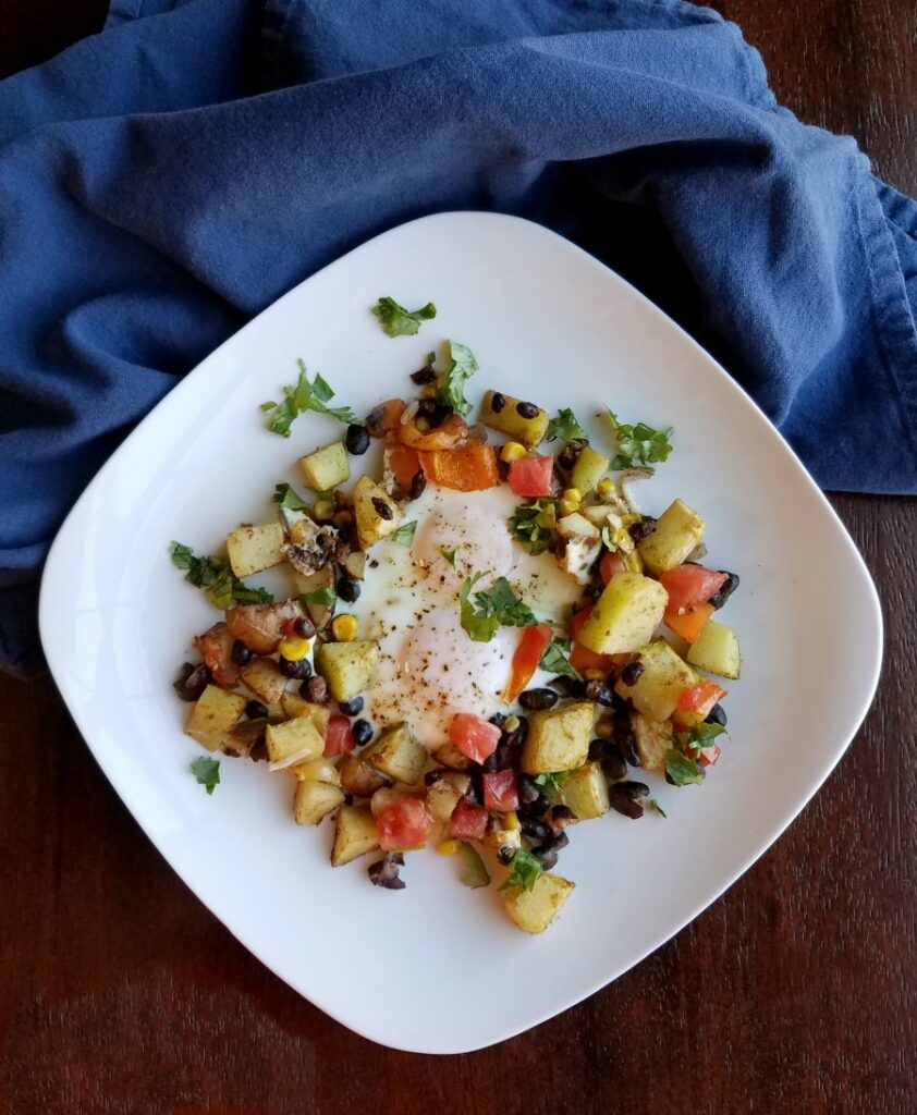 plated filled with vegetables, eggs and sprinkled with cilantro and hot sauce.