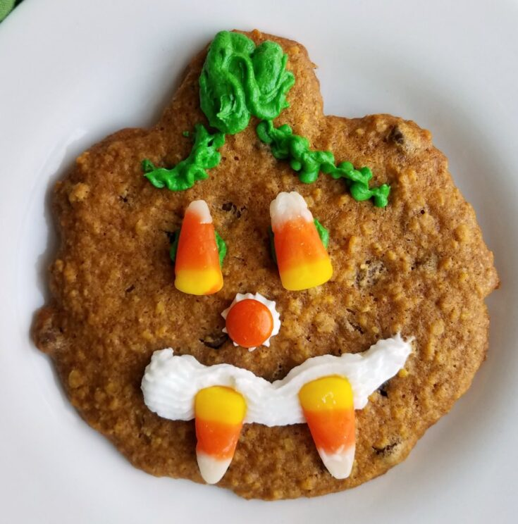 pumpkin oatmeal cookie shaped like pumpkin with frosting and candy jack-o-lantern face on top.