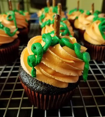 chocolate cupcakes with orange frosting, pretzel stem and green frosting twirls to look like pumpkin