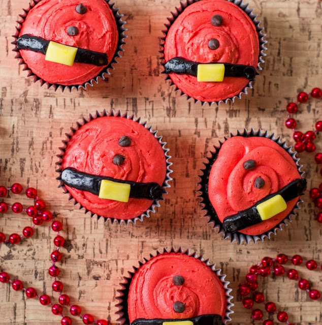 cupcakes with red frosting, chocolate chip buttons and frosting belts to look like santa bellies