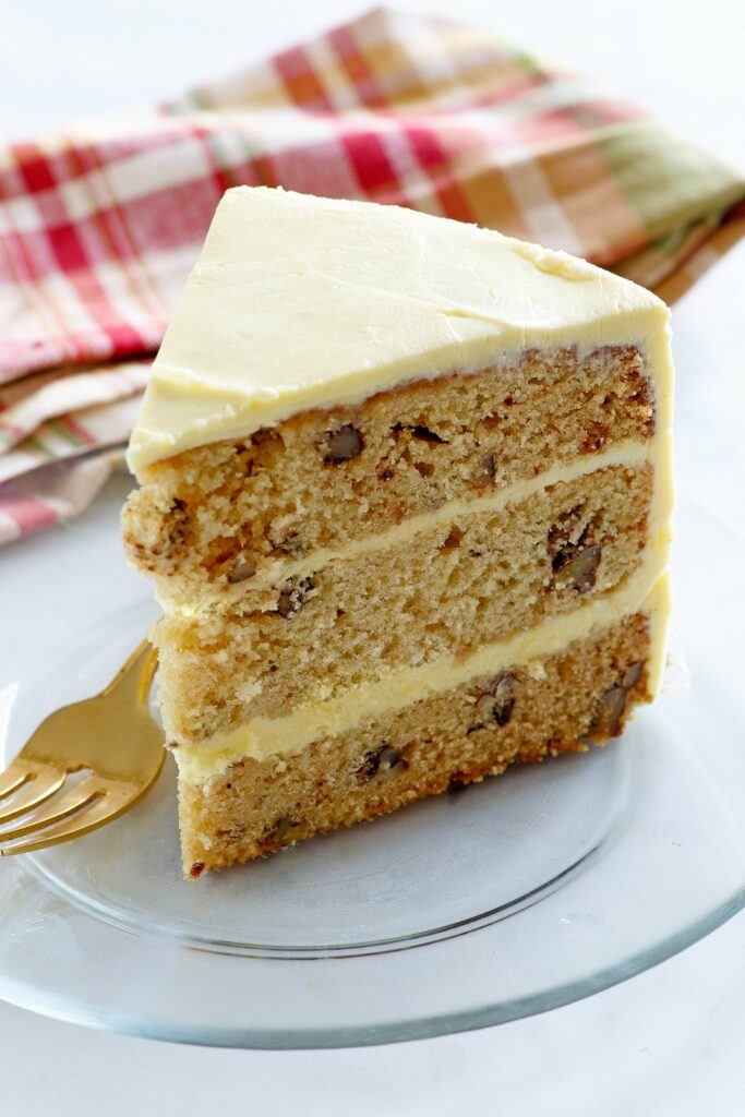 slice of three layer cake with maple and pecans with maple frosting.