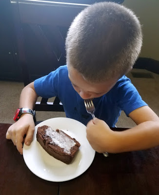 kid eating a piece of bread with butter spread on it