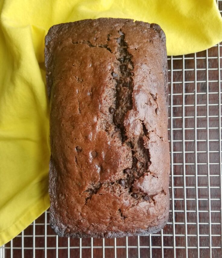 loaf of chocolate banana sourdough quick bread on cooling rack.