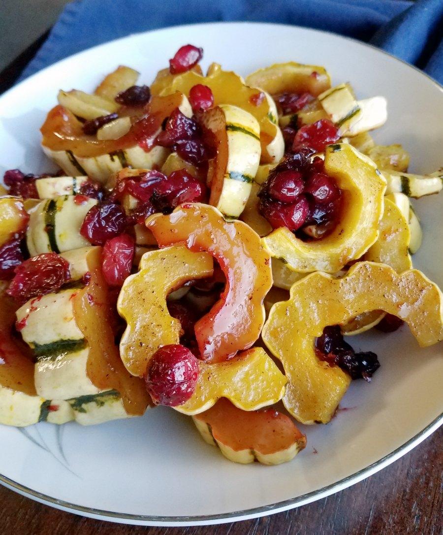 pile of delicata squash crescents with cranberries