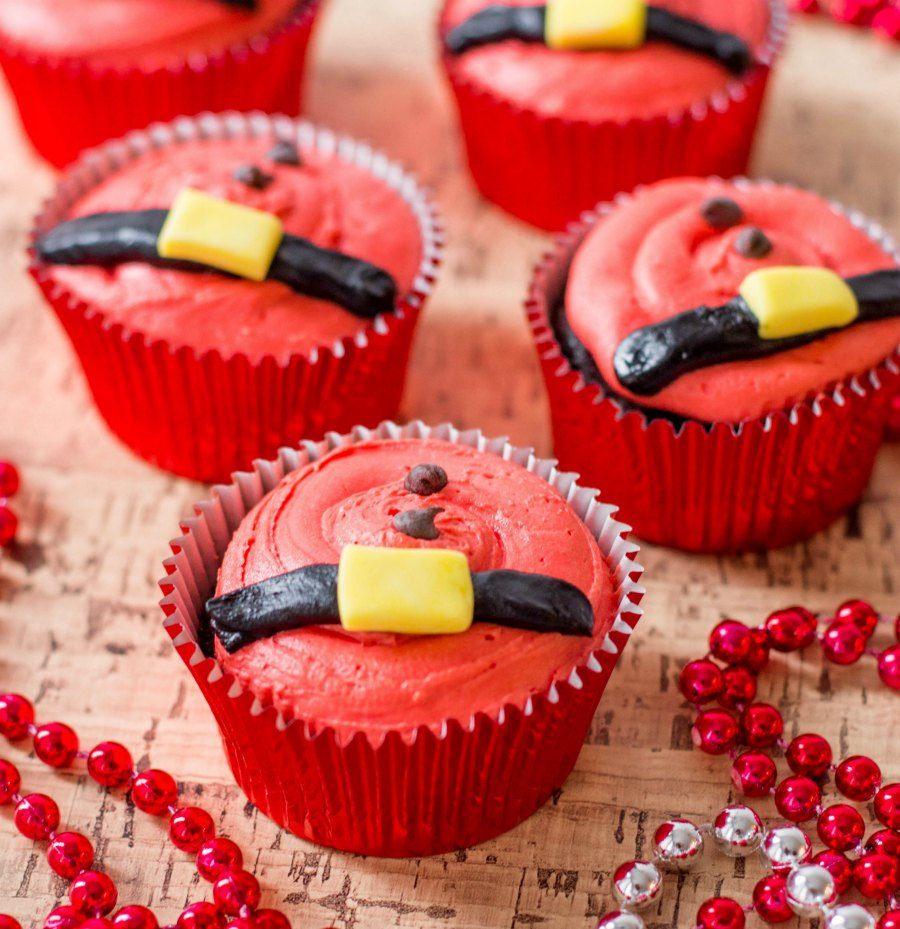 cupcakes decorated with santa belts and chocolate chip coat buttons.