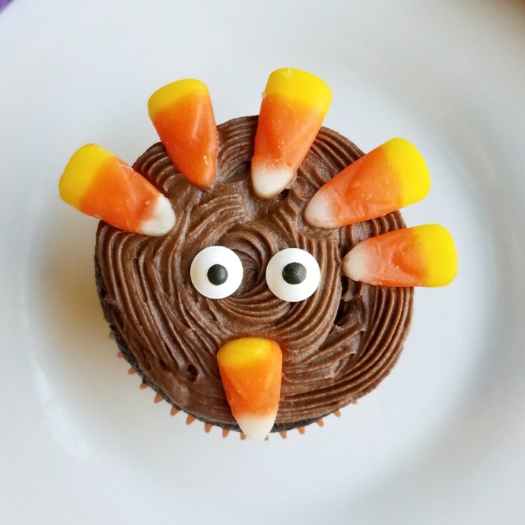 tom the turkey cupcake with eyes and candy corn candies.
